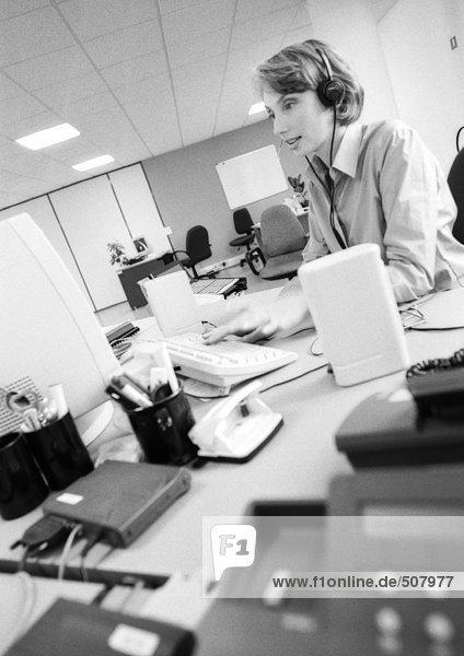 Businesswoman wearing headset in office  side view  B&W