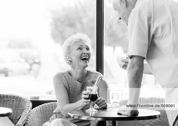 Reife Frau sitzt am Tisch und schaut auf den reifen Mann in einem Cafe  B&W
