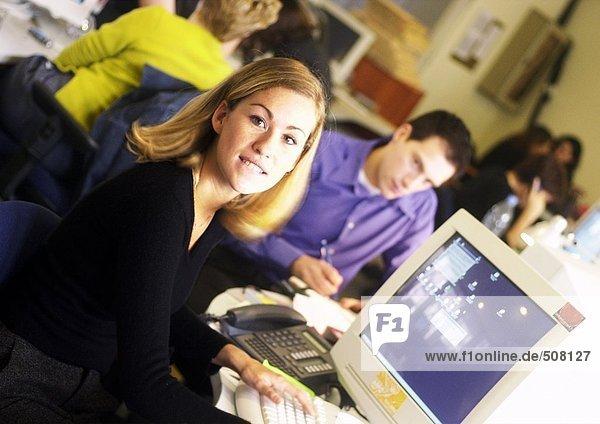 Frau sitzt am Computer im Büro  schaut in die Kamera  Kollegen arbeiten im Hintergrund