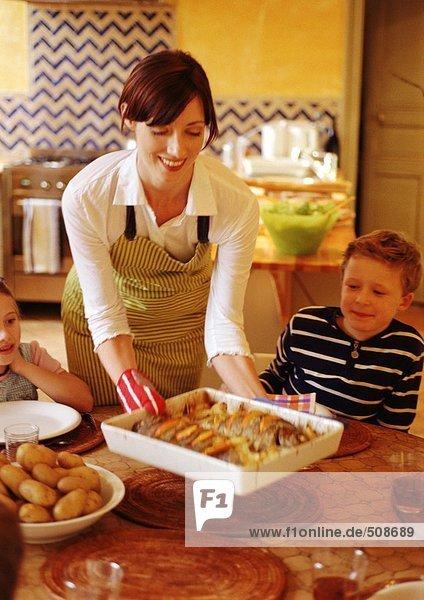 Frau lächelt und stellt Kasserolle auf den Tisch  Kinder sitzen am Tisch