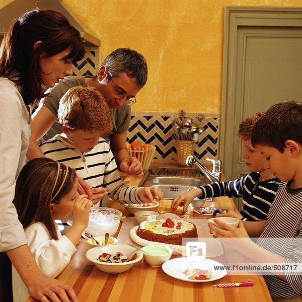 Familie  die um den Tresen steht  Toppings auf einem Kuchen zusammenstellen  Seitenansicht