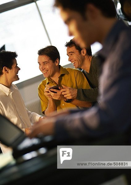 Three men smiling  one holding a hand held computer  fourth man using laptop in foreground