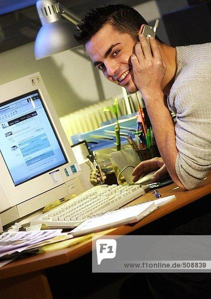 Mann am Schreibtisch sitzend mit Handy