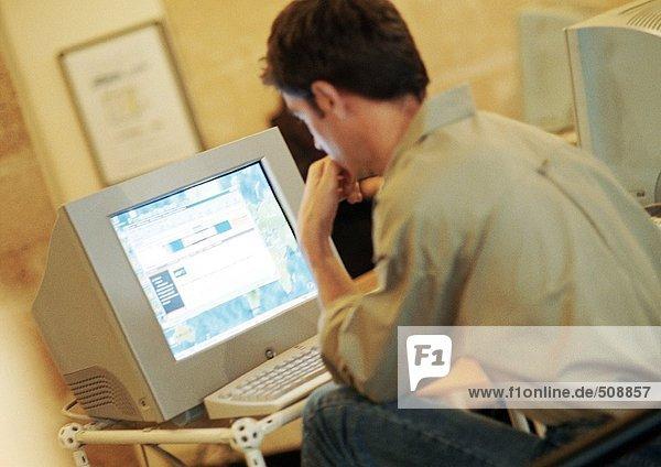 Mann bei der Arbeit am Computer  Rückansicht