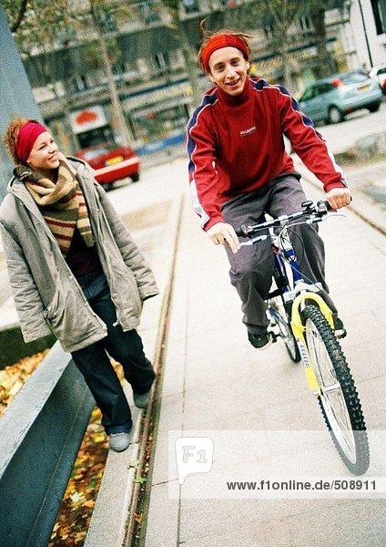 Zwei Jugendliche auf dem Bürgersteig  einer auf dem Fahrrad