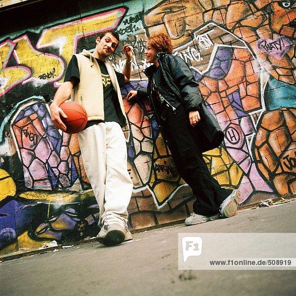 Junger Mann und junge Frau lehnen sich an die graffitierte Wand.