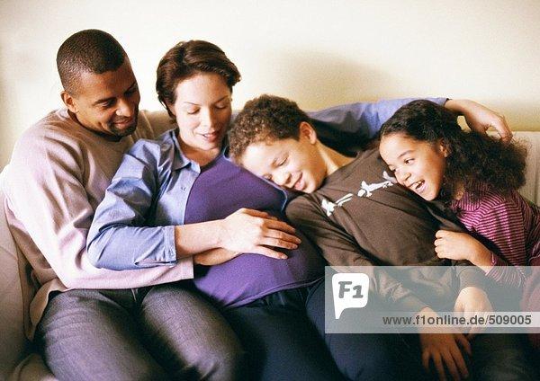 Paar und Kinder auf dem Sofa sitzend