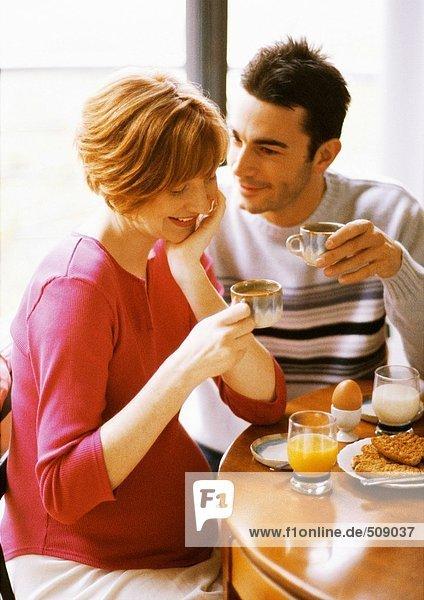 Schwangere Frau und Mann beim Frühstücken  lächelnd