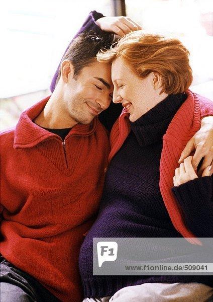 Mann und schwangere Frau sitzend mit Armen umeinander