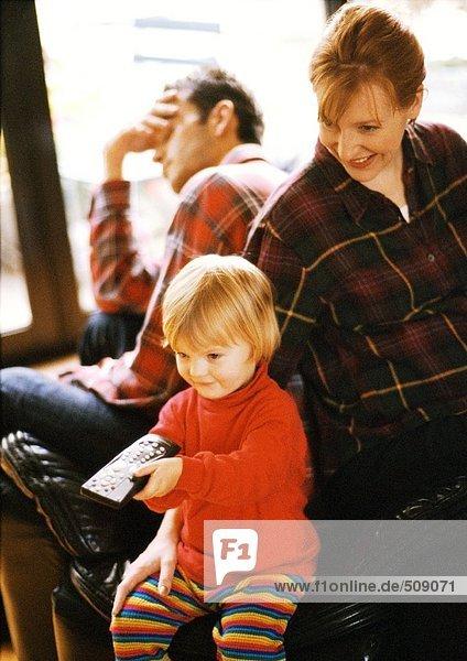 Kind sitzt vor den Eltern und zeigt auf die Fernbedienung.