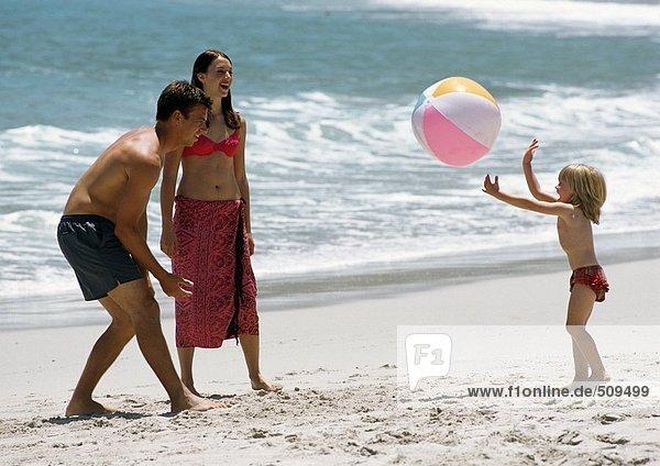 Junge Familie spielt mit Strandball am Strand