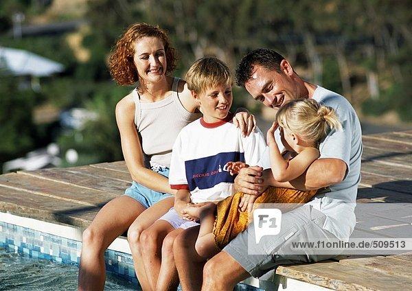 Junge Familie  gekleidet  am Rande des Pools sitzend.