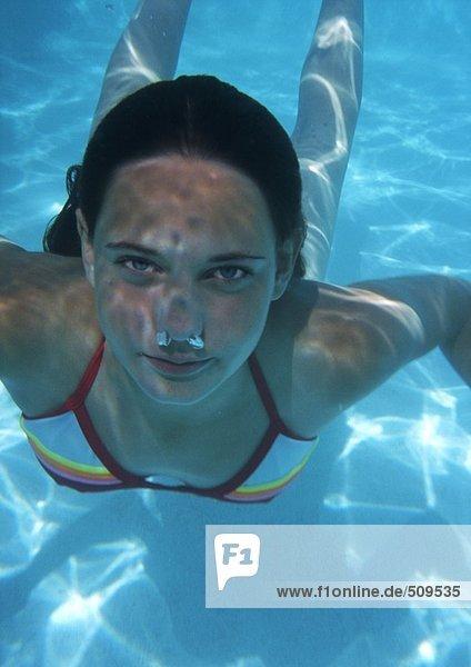 Nahaufnahme eines Teenagermädchens  das unter Wasser schwimmt  Blasen kommen aus der Nase.