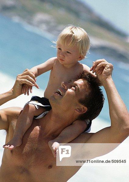 Ein Mann  der das kleine Kind auf seinen Schultern am Strand betrachtet.