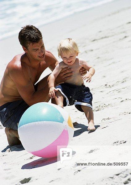 Mann und Kind spielen mit Strandball am Strand.