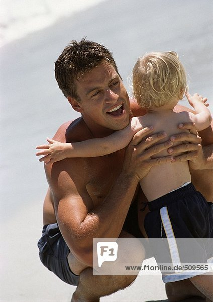 Rückansicht des kleinen Kindes  das den Mann am Strand umarmt.