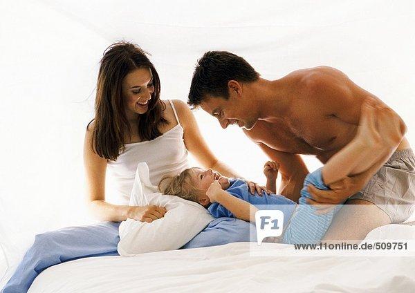 Eltern und kleines Mädchen im Bett  lachend