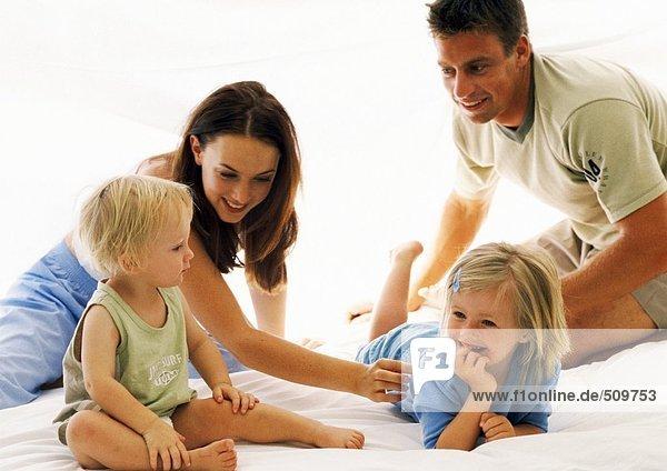 Familie zusammen im Bett  Eltern kitzeln kleines Mädchen