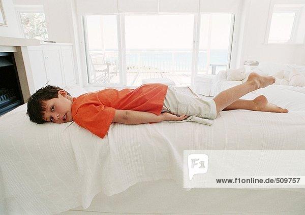 Junge auf dem Bett auf dem Bauch liegend