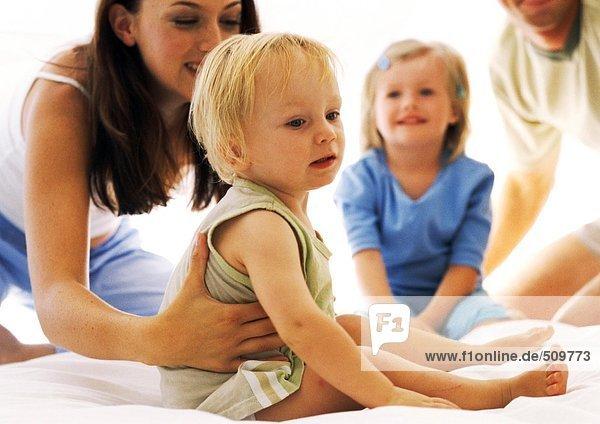 Frau hält Kleinkind im Bett  Familie im Hintergrund