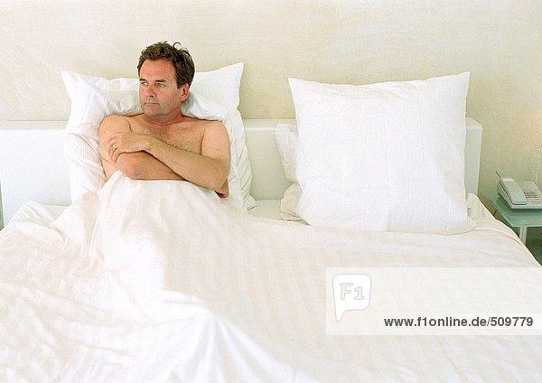 Mann im Bett liegend  Arme über der Brust gefaltet