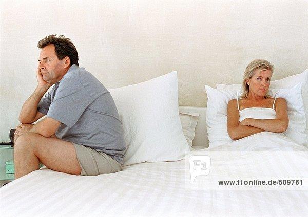 Frau im Bett mit gekreuzten Armen  Mann auf der Bettseite sitzend