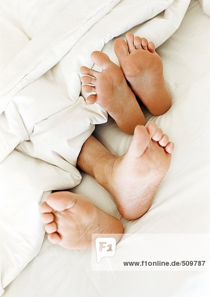 Zwei Paar nackte Füße  die aus der Decke ragen  Nahaufnahme