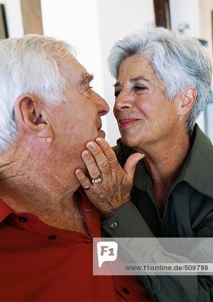 Seniorenpaar  Frau streichelt das Gesicht des Mannes