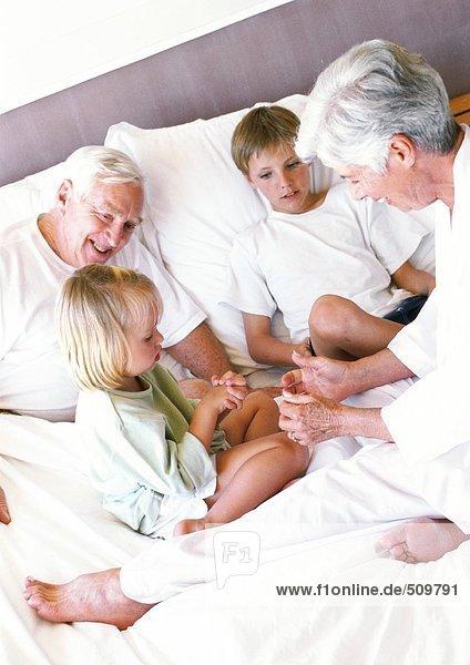 Großeltern und Kinder auf dem Bett sitzend