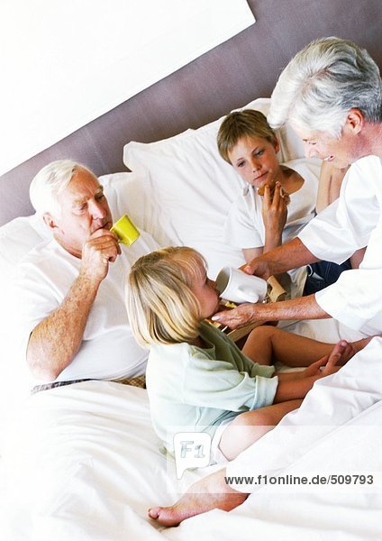 Großeltern und Kinder beim Frühstücken im Bett  Frau hilft dem kleinen Mädchen beim Trinken aus der Tasse