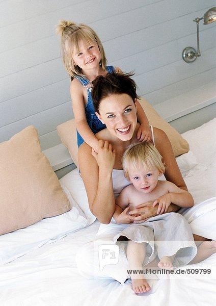 Mutter und Kinder im Bett  lächelnd vor der Kamera