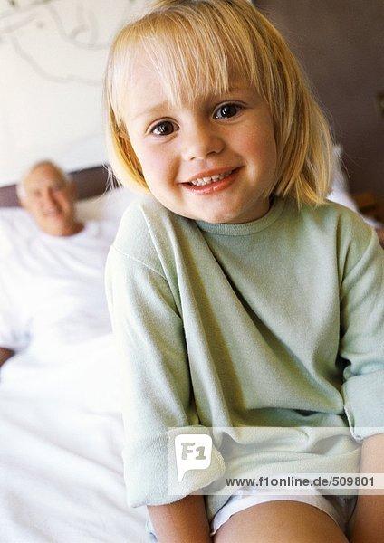 Kleines Mädchen im Bett  lächelnd vor der Kamera  Großvater im Hintergrund