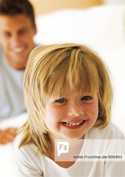 Kleines Mädchen lächelt in die Kamera  Vater im Hintergrund