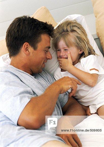 Vater und Tochter auf dem Bett  spielend