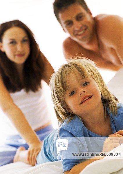 Mädchen im Bett  Eltern im Hintergrund