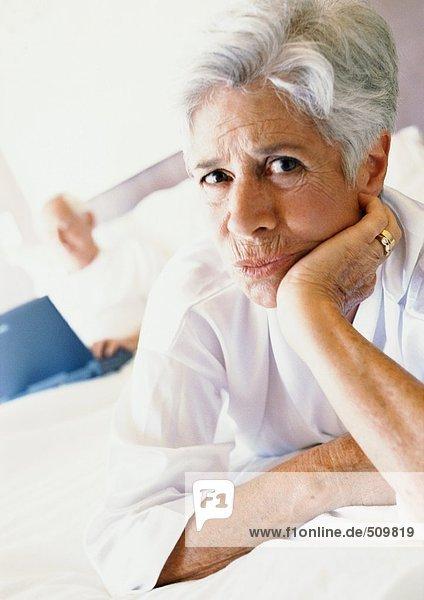 Seniorin im Bett mit Hand unter dem Kinn  Mann mit Laptop im Hintergrund