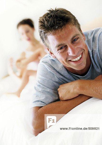Mann lächelnd  Frau und Kind im Hintergrund
