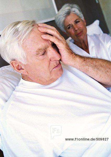 Seniorenpaar im Bett  Mann mit Hand im Gesicht