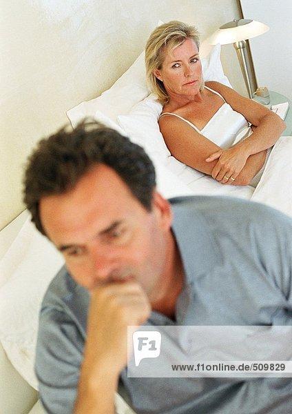 Paar im Bett  Frau mit gefalteten Armen  Mann hält Kopf