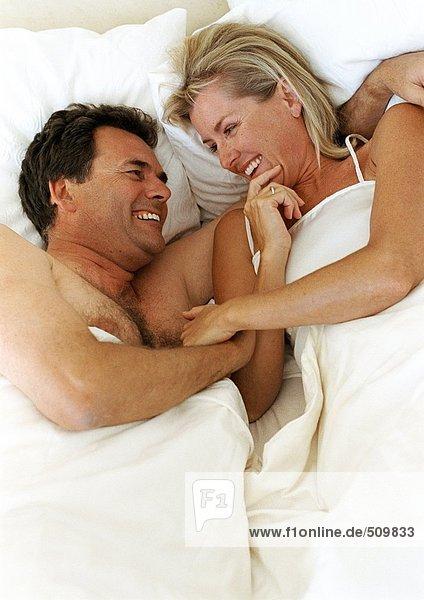 Paar im Bett liegend lächelnd und lachend