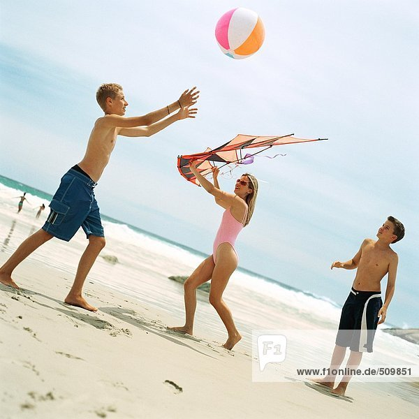 Zwei Jungen spielen mit Strandball  Frau hält Drachen