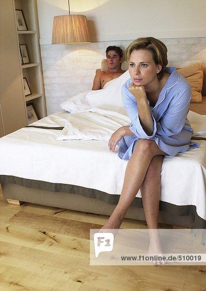 Mann im Bett liegend  Frau am Ende des Bettes sitzend