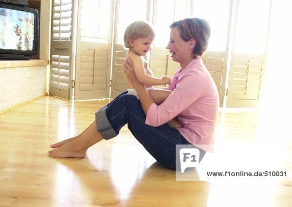 Frau auf dem Boden sitzend  Baby haltend