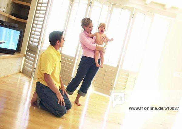 Frau hält weinendes Baby  Mann auf dem Boden kniend