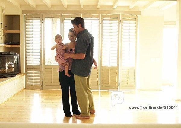 Paar steht im Zimmer mit Baby