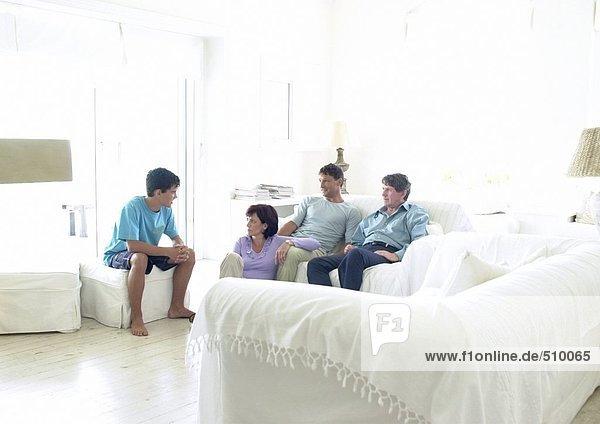 Familie sitzend im Wohnzimmer