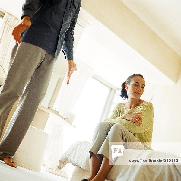 Mann stehend mit ausgestreckten Händen  neben Frau auf dem Bett sitzend und wegschauend  niedriger Blickwinkel