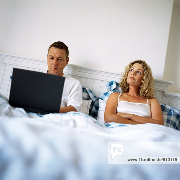 Paar im Bett  Mann mit Laptop  Frau mit gekreuzten Armen