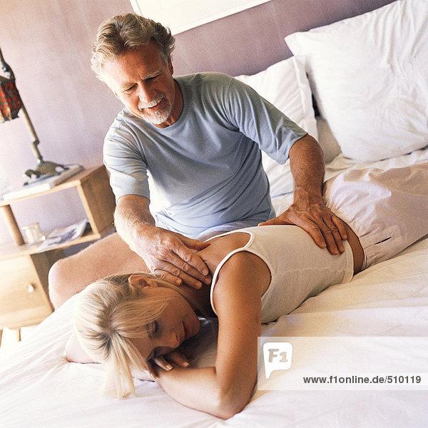 Reifer Mann massiert Frau auf dem Bett