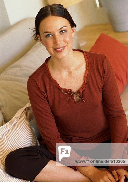 Frau auf Sofa sitzend  lächelnd  Porträt